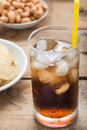 Cold cola iced drink in a glasses on a wood background.