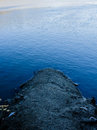 Into the cold depths a concrete pillar dives frigid blue waters Stock Photography