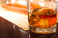 A cold drink transparent ice cubes in glass of whiskey on the table Royalty Free Stock Images