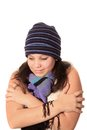 Cold girl wearing a wool hat and scarf but bare sleeves holding herself as if or freezing Stock Photo