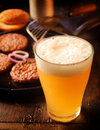 Cold glass of frothy beer with burger patties standing alongside a pan grilled beef in a pub or restaurant high angle focus to Stock Photo