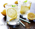 Cold glasses of fresh lemonade shot with selective focus on wood table Stock Photos