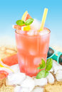 Cold grapefruit juice with ice on beach background in a tall glass mint leaves and cubes sand bar summer holiday beverages menu Stock Image