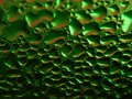A cold green bottle can be a beer with water droplets on a surface shot close-up and a macro refreshing background image or patter Royalty Free Stock Photo