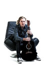 Cold hands holding the guitar image ofa caucasian man with long blond hair sitting on a big black leather chair a guiter between Royalty Free Stock Image