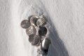 Cold hard cash - silver coins in snow Royalty Free Stock Photo