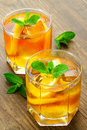 Cold iced tea lemon on brown wooden table with mint around Royalty Free Stock Image