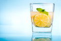 Cold lemonade in a glass with ice on a blue background Royalty Free Stock Photos