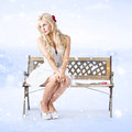 Cold and lonely winter woman sitting all alone girl on park bench under falling snow with a single red rose by her side Stock Images