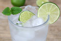 Cold mineral water drink with lime ice cubes and Royalty Free Stock Photos