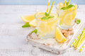 Cold refreshing summer drink with lemon and mint on wooden background. Royalty Free Stock Photo