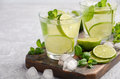 Cold refreshing summer drink with lime and mint in a glass on a grey concrete or stone background. Royalty Free Stock Photo