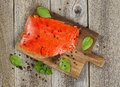 Cold smoke red salmon being prepared on wooden server board Royalty Free Stock Photo