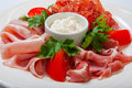 Cold smoked meat plate with prosciutto, salami, bacon, ham and sauce on a white plate. Royalty Free Stock Photo