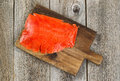 Cold Smoked Red Salmon on wooden server board with rustic wood b Royalty Free Stock Photo