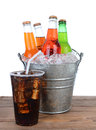 Cold soda bottles in a bucket full of ice picnic table ready for summertime picnic glass cola with straw Royalty Free Stock Photo