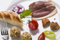 Cold starter with smoked ham liver bon bon and greaves decor decorated on plate vegetables bread Stock Image