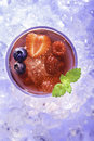 Cold summer drink refreshment with berries mint and soda on ice cubes Stock Photos