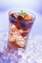 Cold summer drink refreshment with berries mint and soda on ice cubes Stock Photo