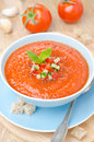 Cold tomato soup gazpacho with basil in a bowl top view vertical blue Stock Photo