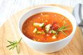 Cold tomato soup gazpacho fresh delicious tasty in white bowl with spoon on wooden board closeup horizontal Stock Photography