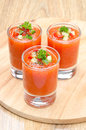 Cold tomato soup gazpacho in portion glasses vertical on a wooden board Stock Image