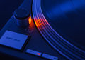 Cold tone look of spinning old fashioned turntable with orange light start and stop speed and power controls Stock Photo