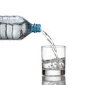 Cold water bottle pour water to glass on white background Royalty Free Stock Photos