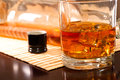 Cold whiskey a glass of with ice and a bottle in the dark lacquered table Royalty Free Stock Images