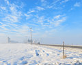 Cold winter day a road leading to a farm on a winters with blue sky and whispy clouds Stock Photography