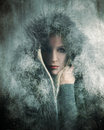Cold winter girl wearing fur in snow a is a coat with falling around her for a weather or warmth concept Stock Photos