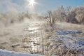 Cold winter morning vapors on the river water looked like pudding flowing down rapids and from were tree high sun Royalty Free Stock Photos
