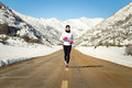 Cold winter running woman female athlete in mountain road training for marathon outdoors wearing warm sportswear Royalty Free Stock Images