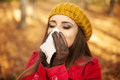 Cold woman sneezing in handkerchief at autumn Royalty Free Stock Photos