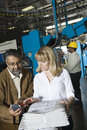 Colleagues with calculator checking newspaper in factory using and worker background at Royalty Free Stock Photography