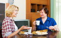 Colleagues drinking tea and talking during coffee break two in years Stock Images