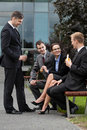 Colleagues having a conversation group of colleaques sitting on bench and talking Royalty Free Stock Image