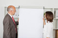 Colleagues looking on white flipchart two standing next to it Royalty Free Stock Photos