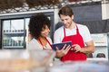 Colleagues in red apron using tablet at the bakery Stock Photo