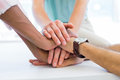 Colleagues show teamwork by bringing hands together in the office Royalty Free Stock Photography