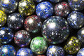 A collection of black blue yellow red and green speckled marbles Stock Photos