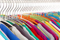 Collection of colored shirts on steel hangers isolate shallow depth field Royalty Free Stock Images