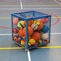 Collection of different balls in a metal cage school gym Royalty Free Stock Images