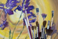 Collection of paint brushes with a painting irises in the background Royalty Free Stock Image