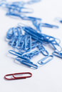 Collection of paperclips in various colours on white with stationary items Royalty Free Stock Photography