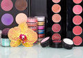 Collection  professional cosmetics for makeup and orchid flower background. Royalty Free Stock Photo