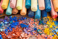 Collection of rainbow colored pastel crayons with crushed chalk Royalty Free Stock Photo