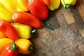 A collection of Red and Yellow Sweet Peppers Bordering Wood Cutt Royalty Free Stock Photo