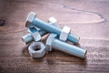 Collection of stainless threaded screw nuts and bolt details on vintage wooden board repairing concept Royalty Free Stock Image