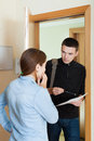 Collector trying to get the arrears from woman women at home door Stock Photo